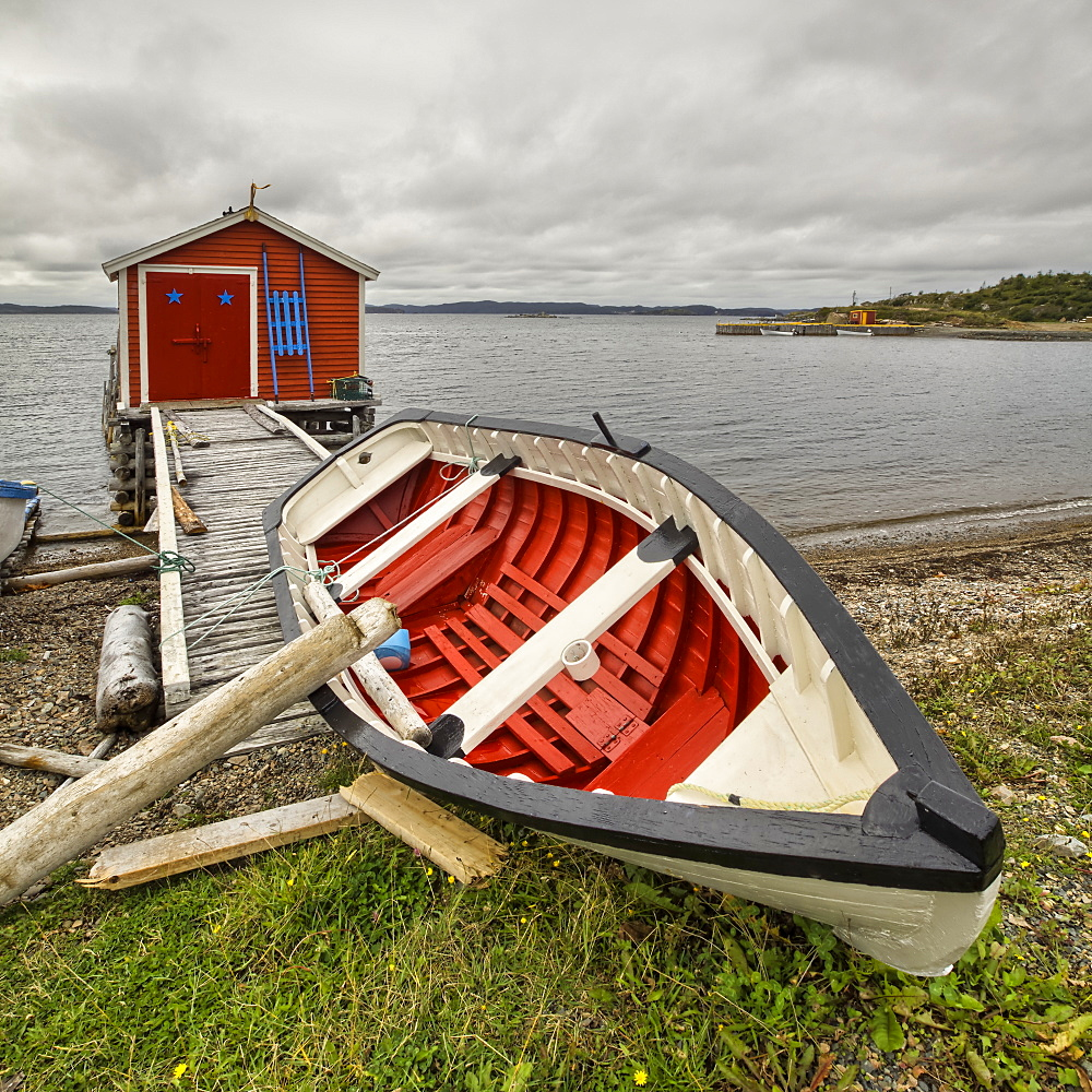 A red and white canoe lays on the shore with a red fishing shed along the water's edge of the Atlantic coast, Newfoundland, Canada