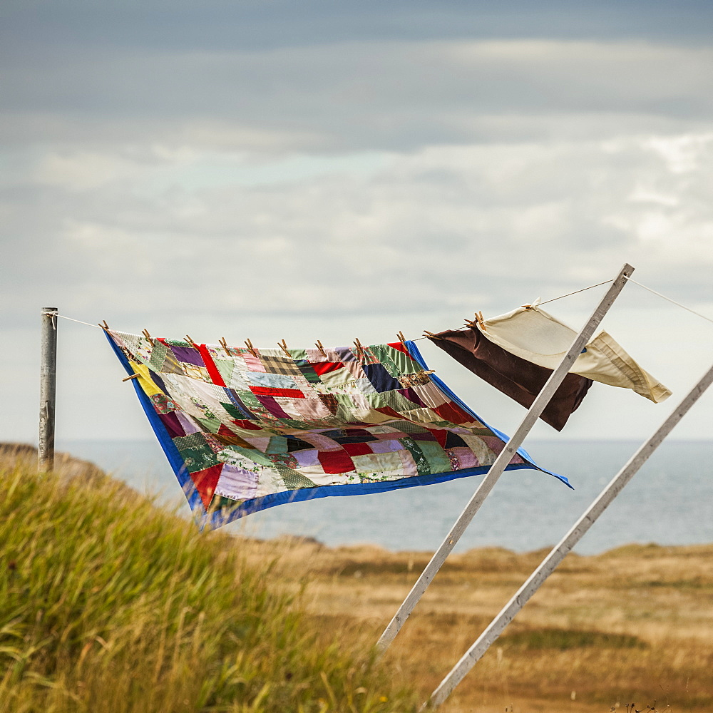 A patchwork blanket and pillow cases hanging on a clothesline with the Atlantic ocean in the background, Newfoundland, Canada