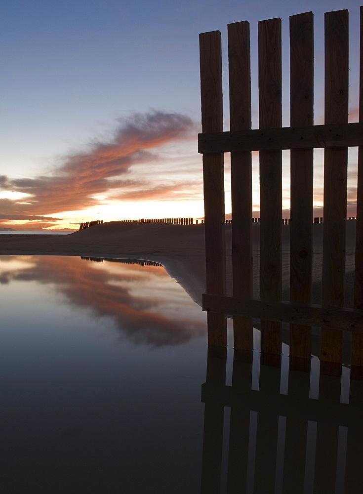 Wooden Fence Along Shoreline Of Beach