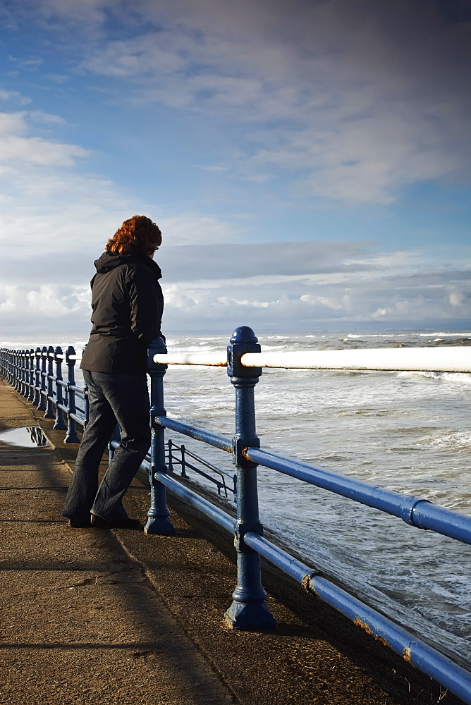 Saltburn, Teesside, England, A Woman Standing At A Railing And Looking Out Over The Ocean