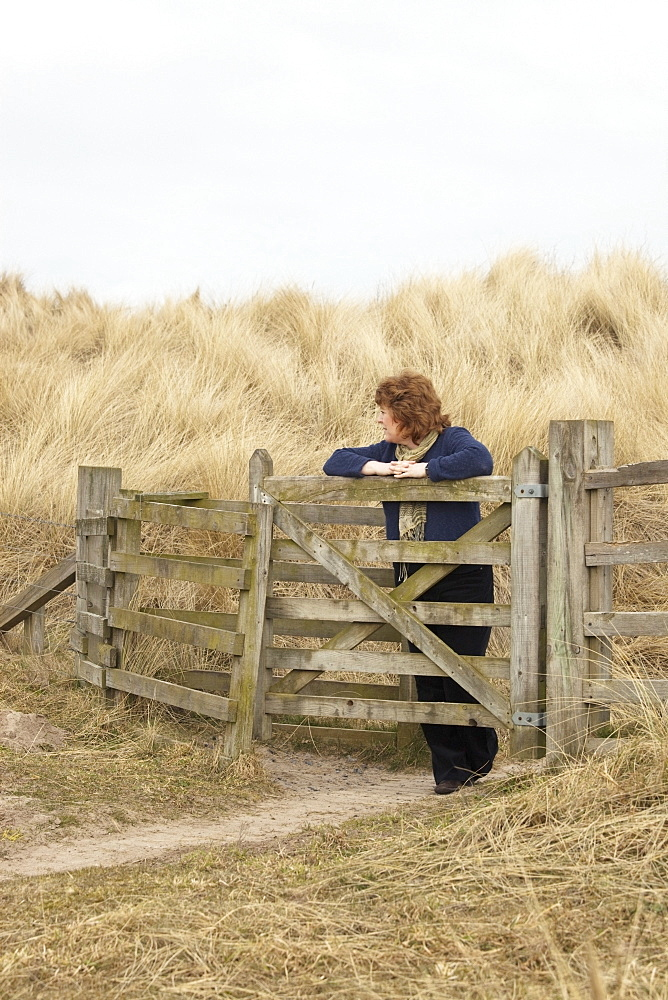 Northumberland, England, A Woman Leaning Against A Fence