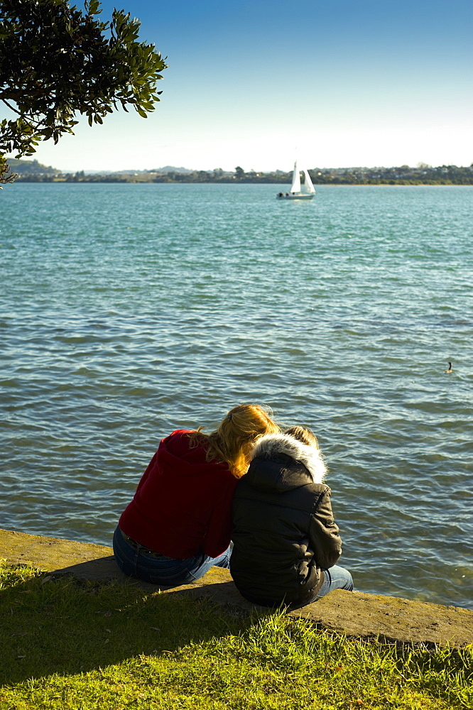 Two Girls Sitting On A Retaining Wall At The Water's Edge, Auckland, New Zealand