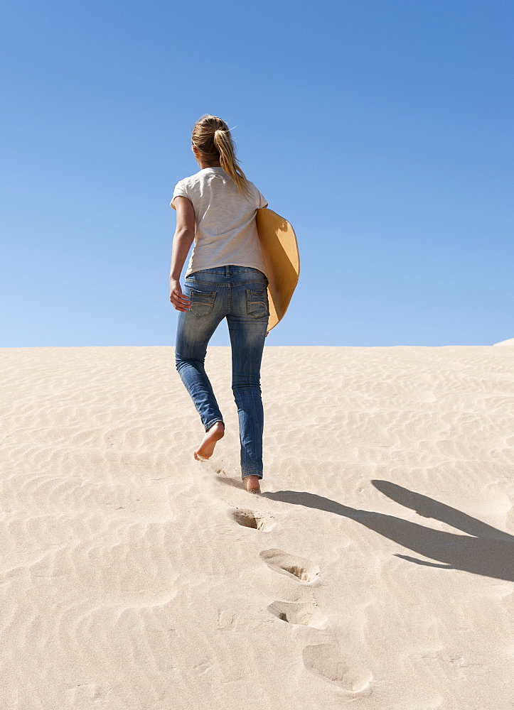 A Young Woman Walks With A Board Over The Punta Paloma Sand Dunes, Tarifa, Cadiz, Andalusia, Spain - 1116-41438