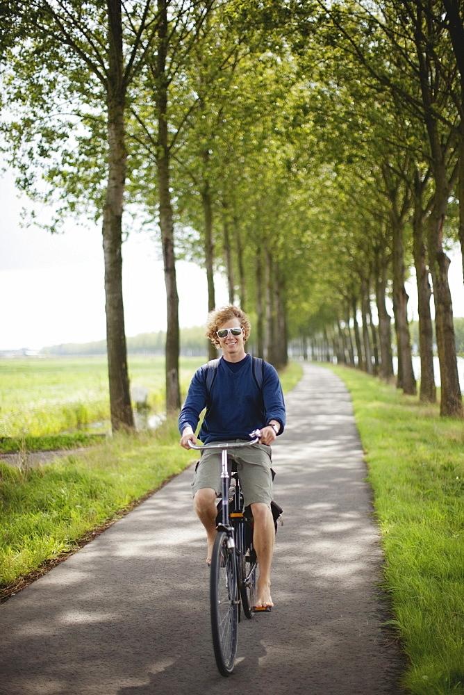 A Boy Riding His Bike Along The Dutch Canals, Houten, The Netherlands
