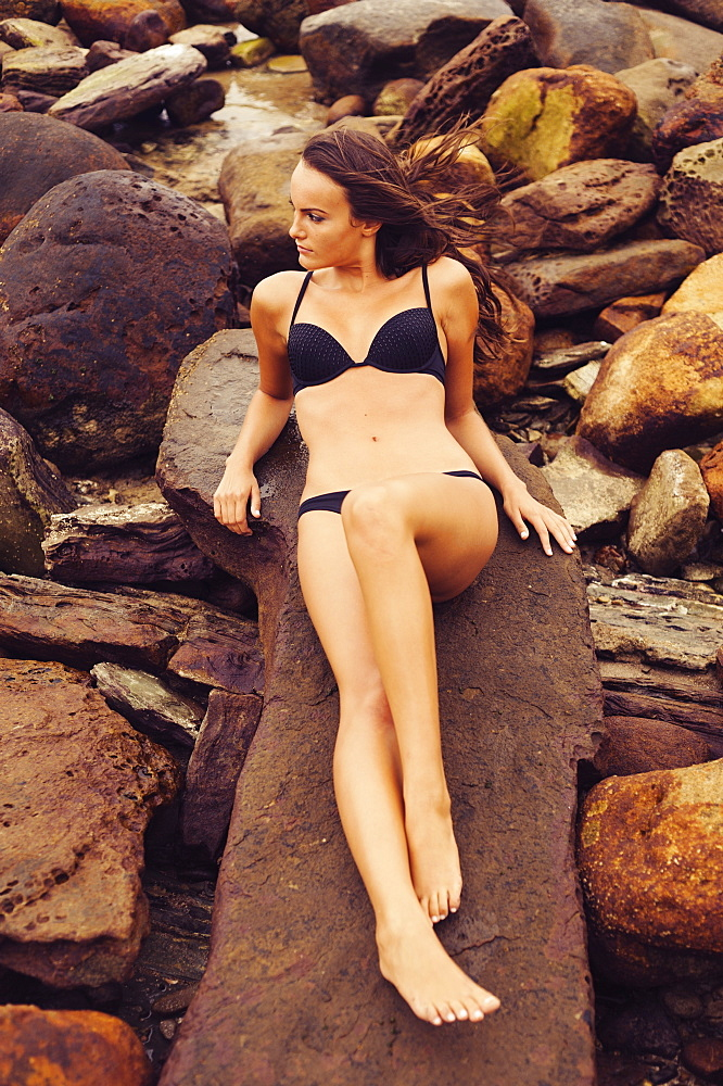 A Woman Wearing A Bikini Laying On A Rock In Parque Natural Del Estrecho, Tarifa, Cadiz, Andalusia, Spain
