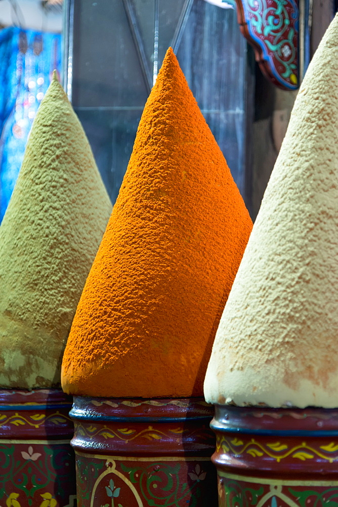 Colourful pots holding conical shapes on top