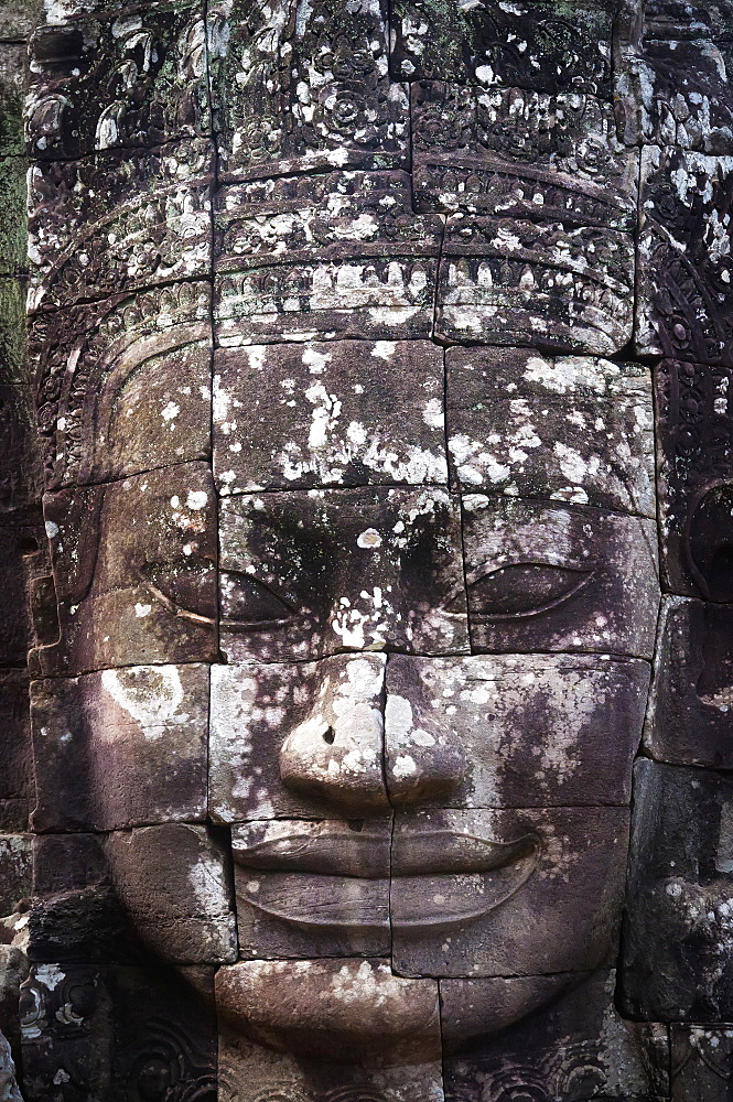 A face sculpture on a stone wall at angkor wat, Cambodia