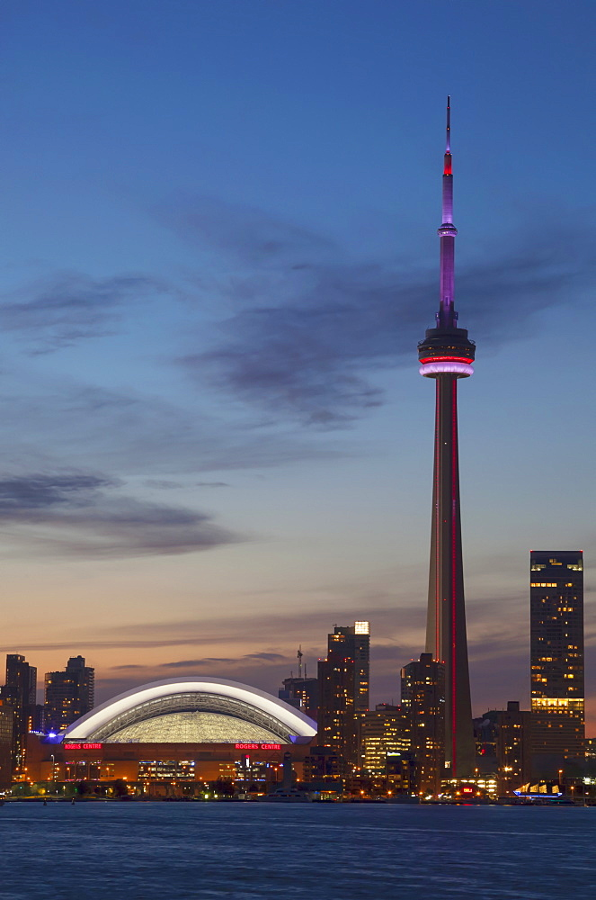 View over lake ontario of the downtown toronto skyline and cn tower illuminated at dusk, Toronto ontario canada
