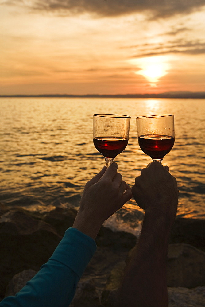 A couple holding wine glasses up at sunset over a lake, Bardolino veneto italy