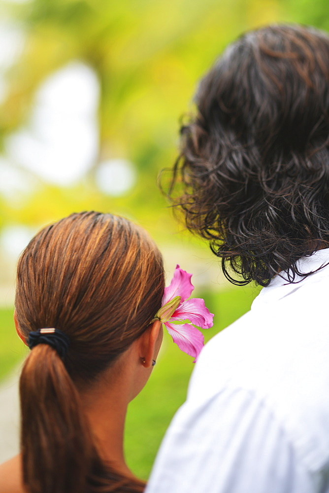 The back of the heads of a man and woman the woman having a flower in her hair bora bora nui resort and spa, Bora bora island society islands french polynesia south pacific