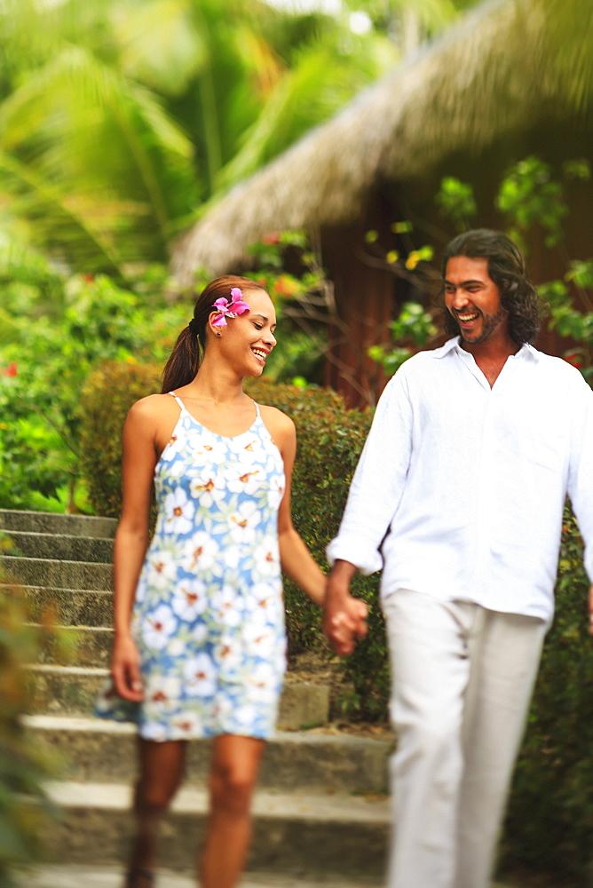 A man and woman hold hands and walk through the bora bora nui resort and spa, Bora bora island society islands french polynesia south pacific