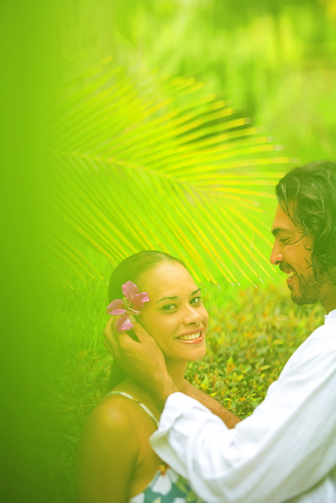 A man puts a flower in a woman's hair at the bora bora nui resort and spa, Bora bora island society islands french polynesia south pacific