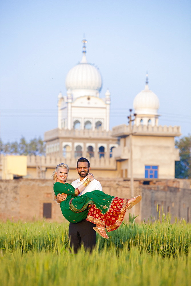 Portrait Of A Mixed Race Couple Her Wearing A Sari With A Temple In The Background, Ludhiana, Punjab, India