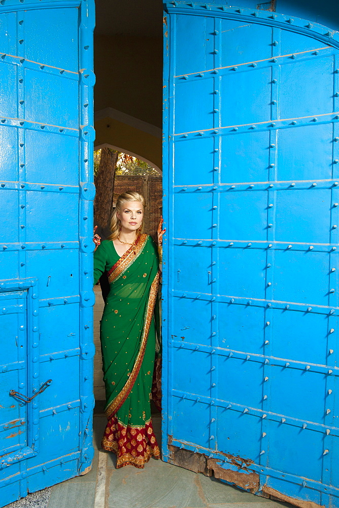Portrait Of A Blond Woman Wearing A Sari Standing In The Doorway With Large Blue Doors, Ludhiana, Punjab, India