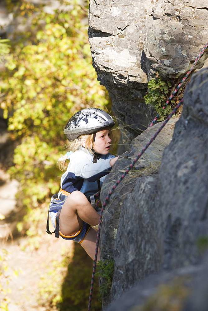 Young Girl (Age 7) Climbing On Granite Cliff At Stone Hills Near Rexford, Montana, Usa