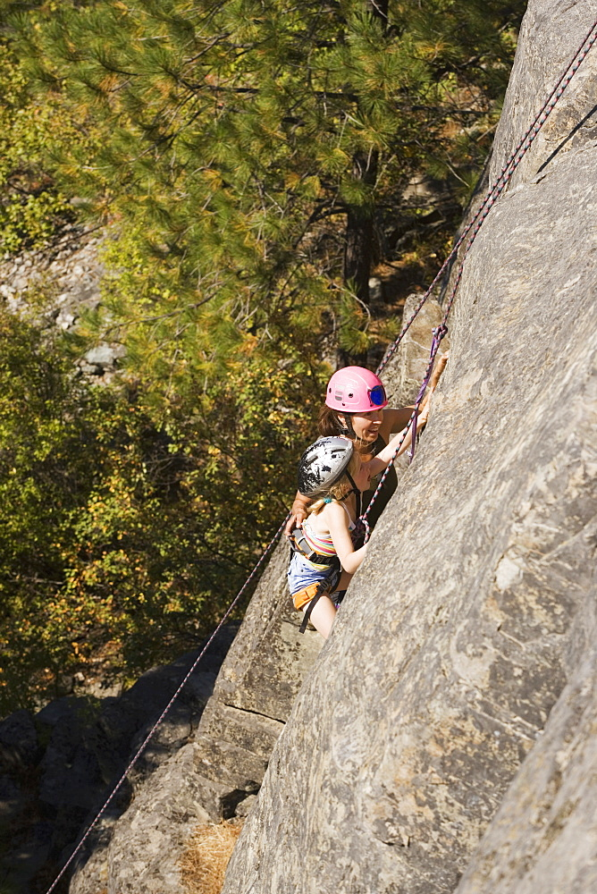Young Woman Climbing With Daughter (Age 7) Up Granite Cliff At Stone Hills Near Rexford, Montana, Usa