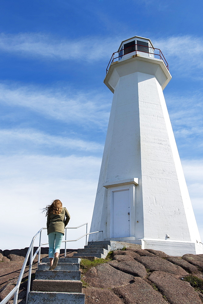 A Young Woman Climbs Steps Towards The Cape Spear Lighthouse, St. John's, Newfoundland And Labrador, Canada