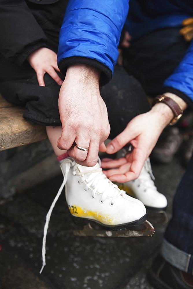 A Father Ties His Child's Ice Skates, Toronto, Ontario, Canada