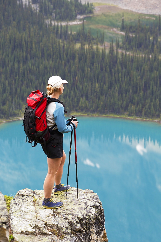 Female Hiker On Rock Cliff Overlooking Blue Alpine Lake, British Columbia, Canada