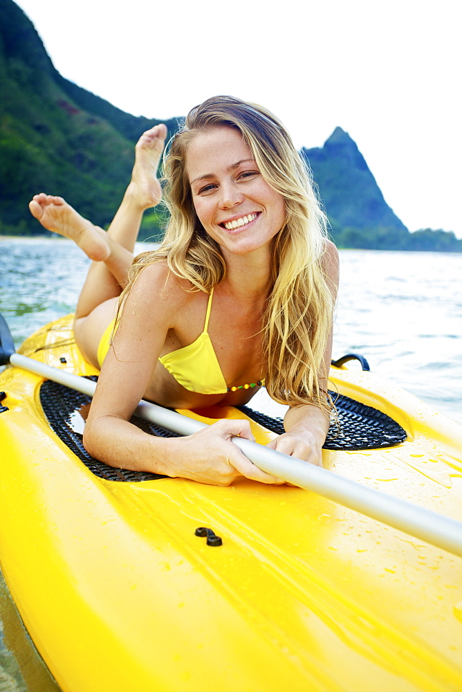 A Young Woman In A Yellow Bikini Laying On A Stand Up Paddleboard, Kauai, Hawaii, United States Of America