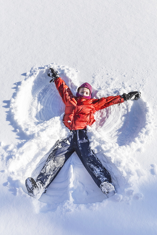 Young Girl Making A Snow Angel In Wintertime, Talkeetna, Alaska, United States Of America