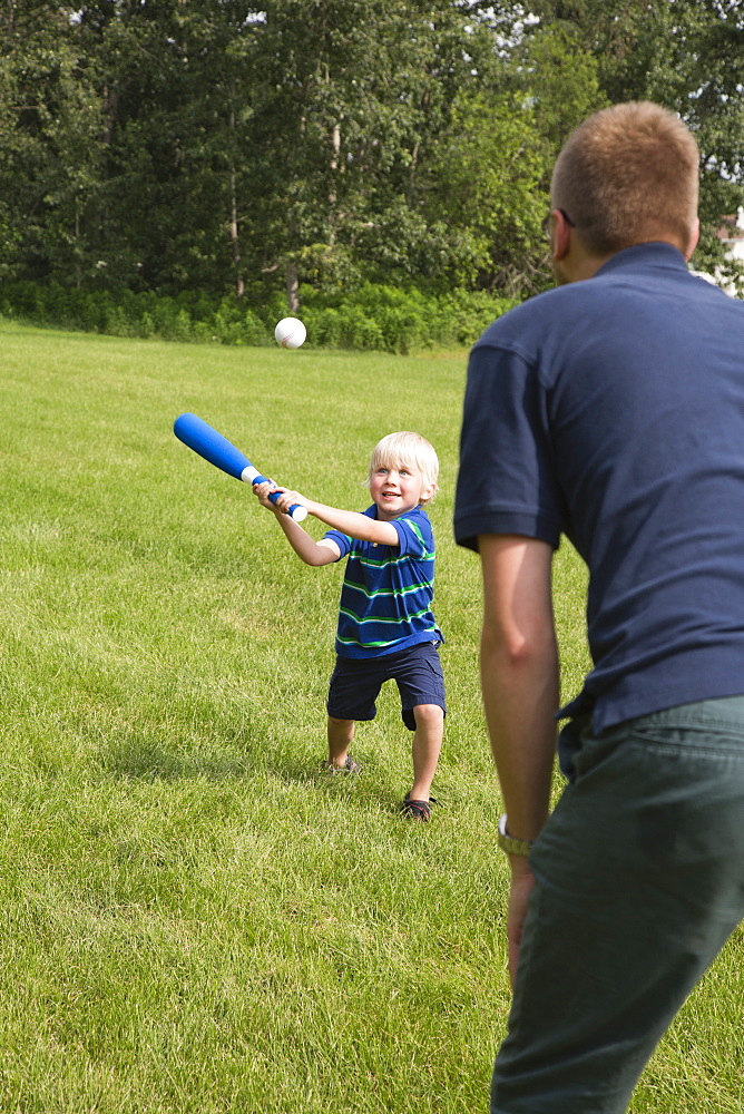 A Father Plays Baseball With His Young Son In The Park, Stony Plain, Alberta, Canada