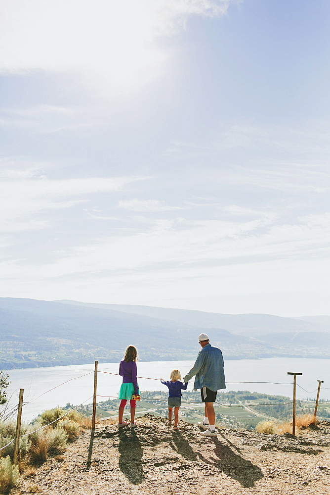 A Family Stands Together Overlooking A View Of Lake Okanagan, Peachland, British Columbia, Canada
