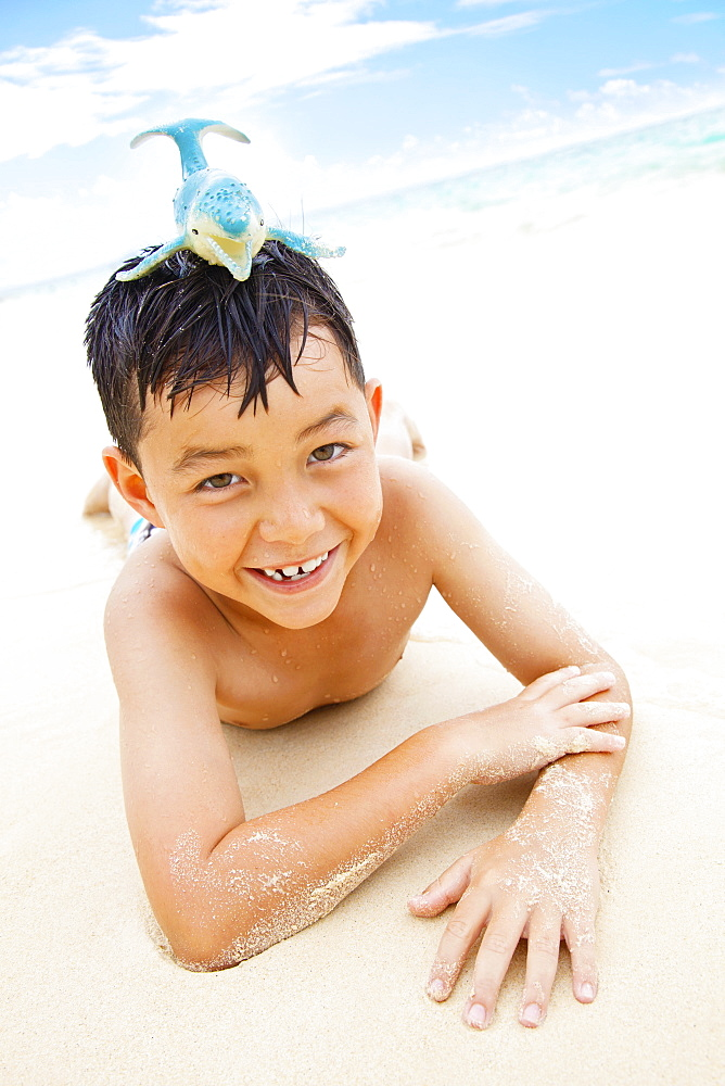 A Boy Laying On The Sand At The Water's Edge With A Toy Whale On His Head, Kailua, Oahu, Hawaii, United States Of America