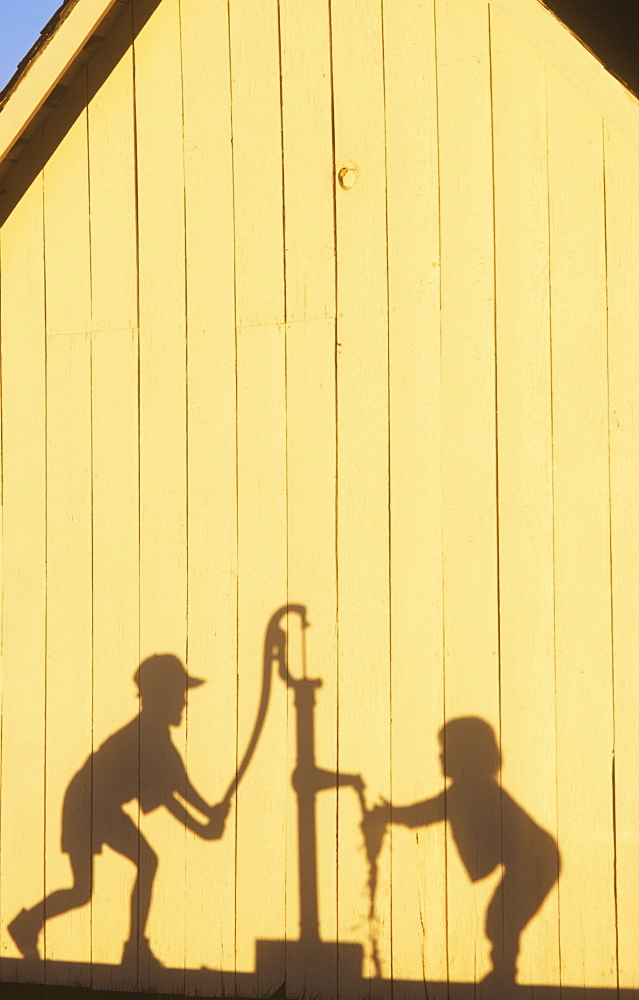 Agriculture - Silhouette on the side of a barn in late afternoon light of a farm boy operating a hand pump water well while his young sister washes her hands / Northwest Missouri, USA.
