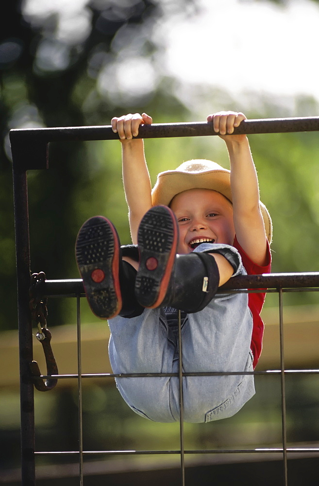 Agriculture - A young farm girl wearing a cowboy hat and rubber boots swings on a metal gate, hanging by her hands and legs and laughing / Northwest Missouri, USA. - 1116-42728