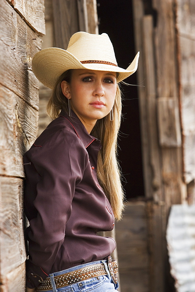 Agriculture - Portrait of a young cowgirl leaning against an old barn / Childress, Texas, USA. - 1116-42765
