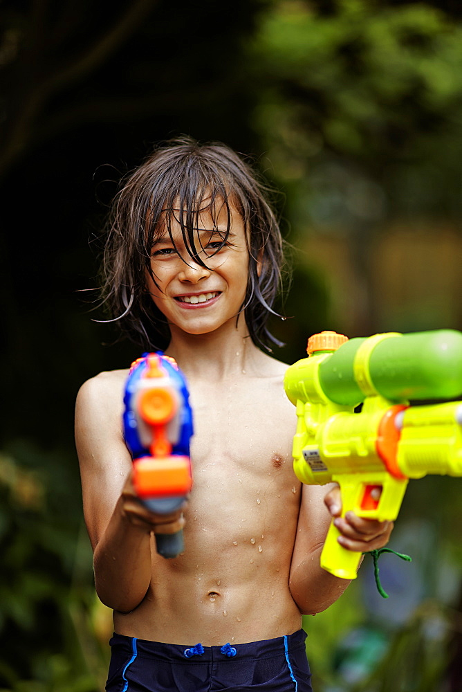 Young Boy Playing With Water Guns, Markham, Ontario, Canada