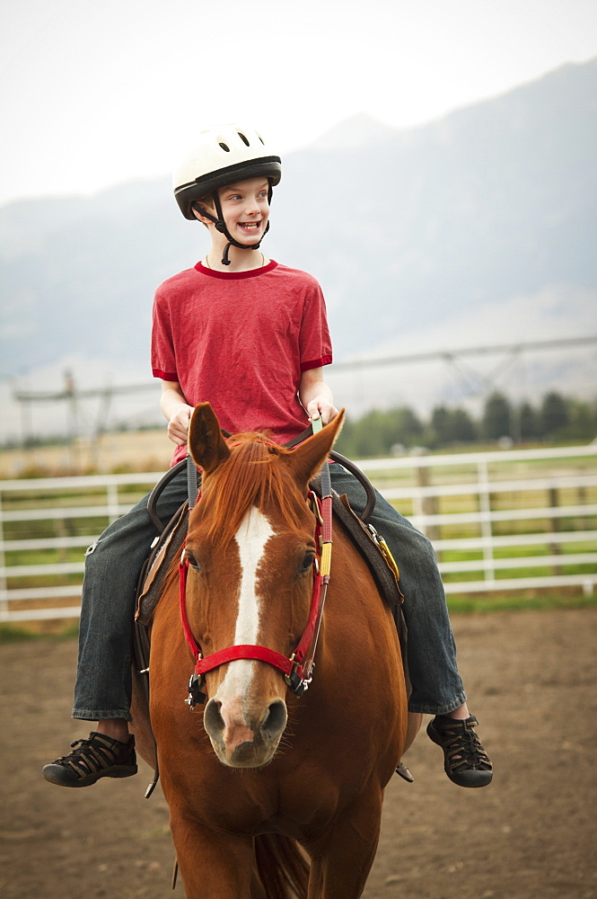 A Young Boy Rides His Horse At Eagle Mount, Bozeman, Montana, United States Of America