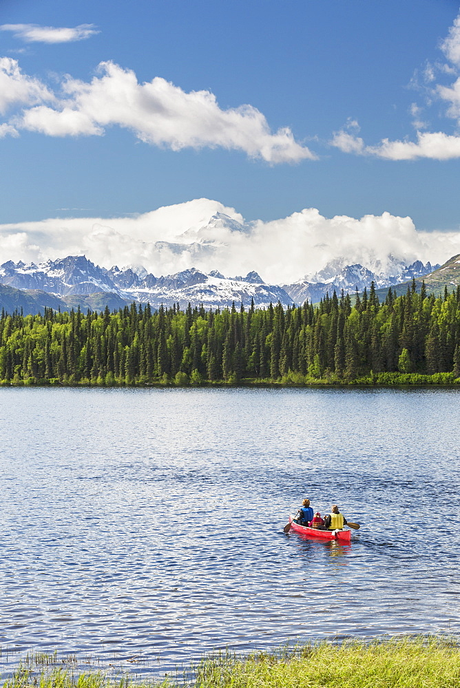 Two Women And Young Girl In A Red Canoe On Byers Lake With Green Forested Shoreline And Mount Mckinley Peaking Through The Clouds, Denali State Park, Alaska, United States Of America