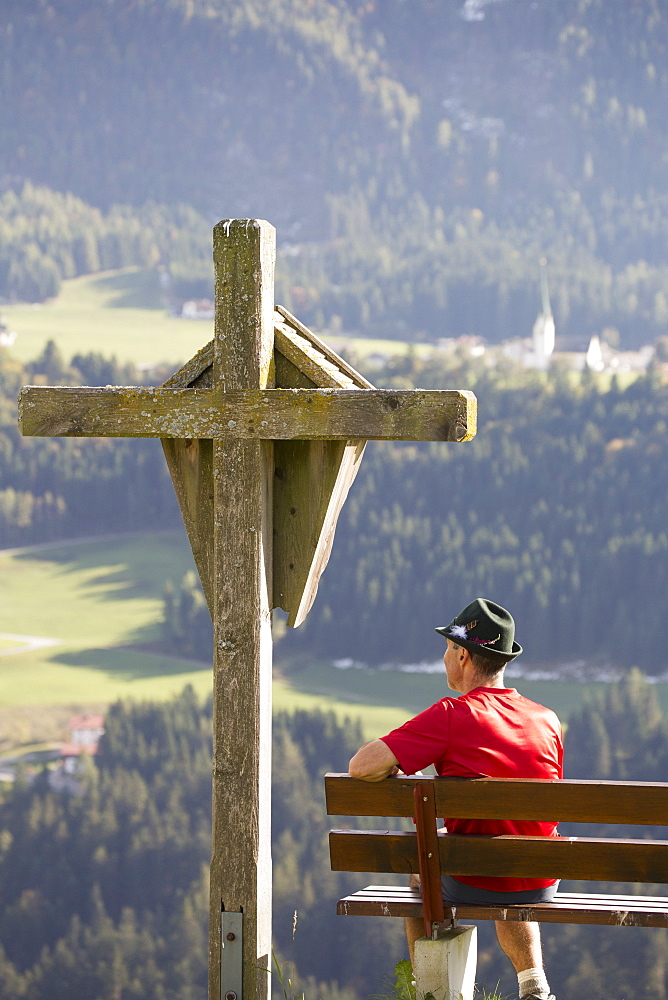Male Hiker Sitting On Bench With Large Wooden Cross Overlooking Valley With Gren Meadows And Trees, Aschau, Austria