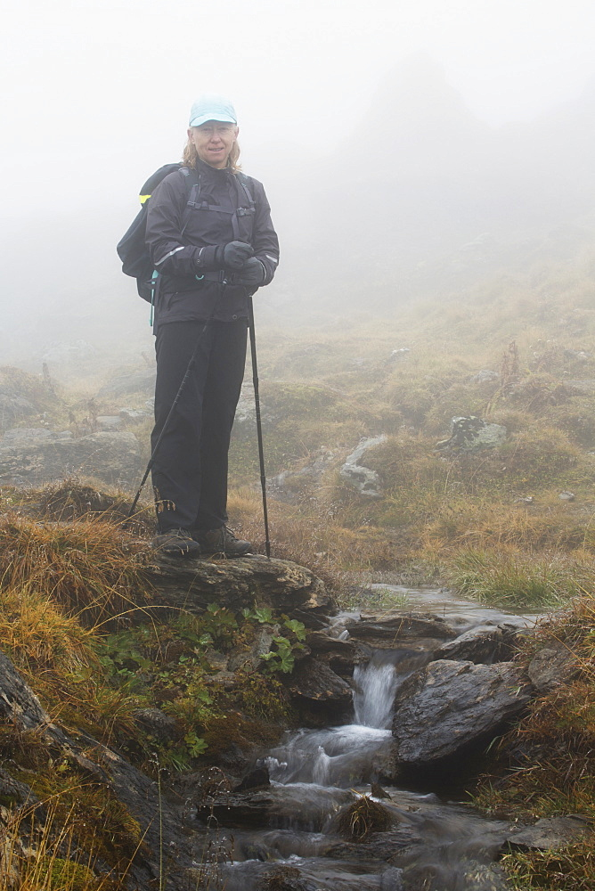 Female Hiker In The Fog Next To A Small Stream Wallfalls In A Grassy Area, Lanserbach, Austria
