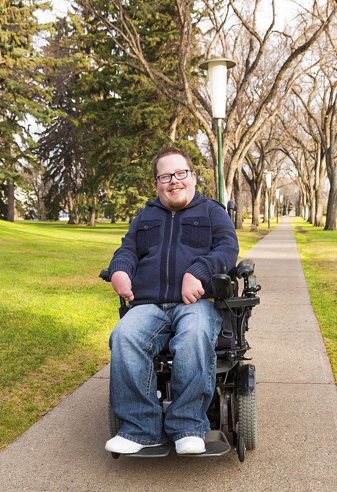 Disabled Man Using His Powered Wheelchair In A Park In Autumn, Edmonton, Alberta, Canada