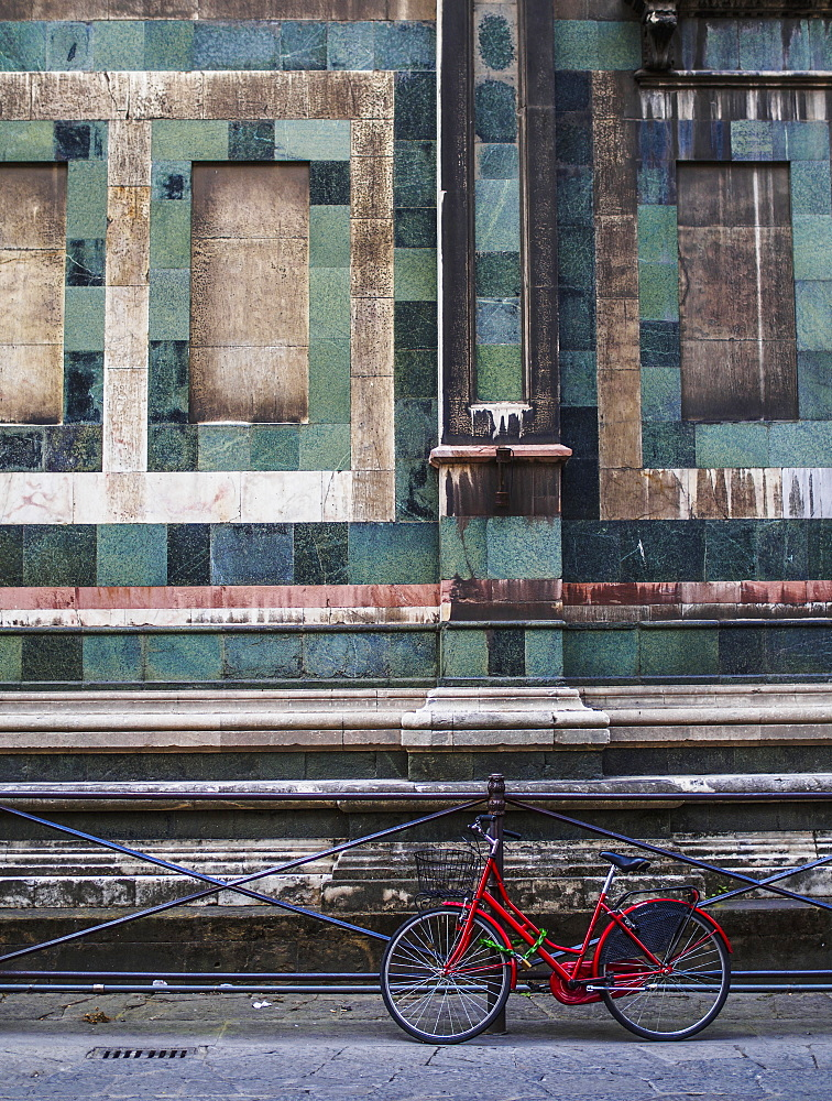 A Red Bike Contrasted With The Green Granite Of The Building Behind It, Florence, Italy