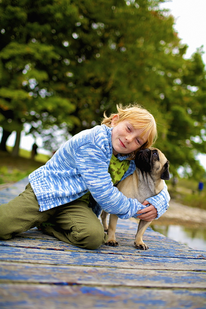 Girl Hugging A Dog On A Dock, Picton, Ontario, Canada