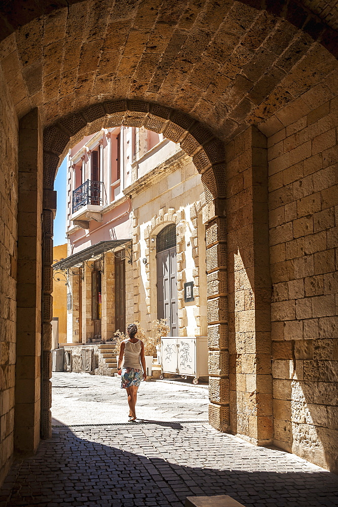 A Woman Walks Through An Arched Walkway, Chania, Crete, Greece