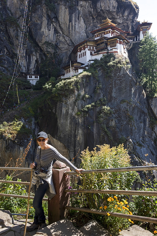 A Woman Stands At A Railing With Taktsang Palphug Monastery In The Background, Paro, Bhutan