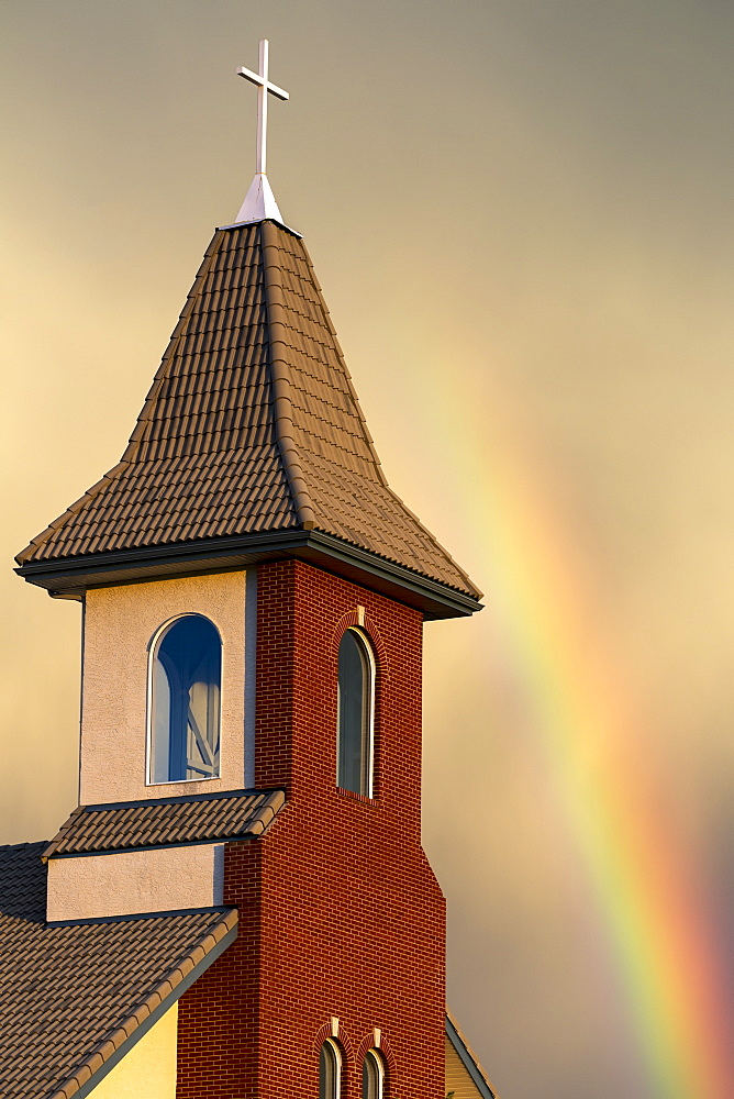 Church Steeple With Orange Glow From The Sunset And Rainbow In The Sky, Calgary, Alberta, Canada