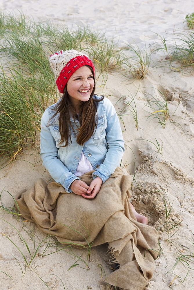 A Young Woman Sits On A Beach Wearing A Knit Hat, Tarifa, Cadiz, Andalusia, Spain