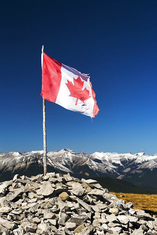 Well Worn Canadian Flag On Wooden Branch Propped In A Pile Of Rocks On Top Of A Mountain With Mountain Range And Blue Sky In The Background, Alberta, Canada