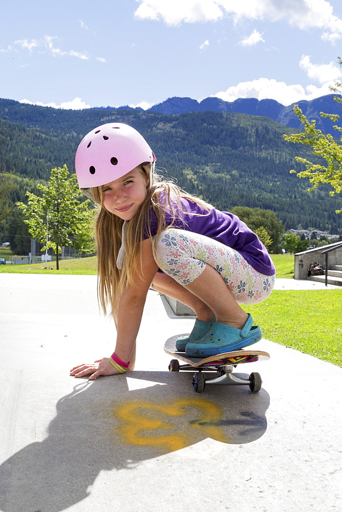 Young Girl On A Skateboard Wearing A Pink Helmet, Salmon Arm, British Columbia, Canada