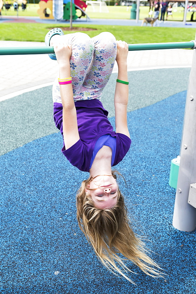Young Girl Hanging Upside Down At The Playground, Salmon Arm, British Columbia, Canada
