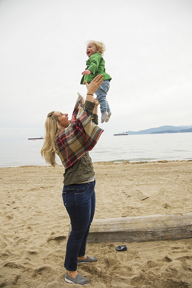 In A Winter Beach Scene, A Mother Joyfully Throws Her Little Girl In The Air, Vancouver, British Columbia, Canada