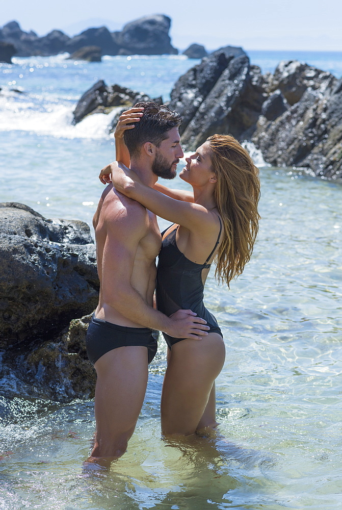 A Couple Standing In The Shallow Water Along The Rocky Coast Wearing Swimwear In An Embrace, Tarifa, Cadiz, Andalusia, Spain