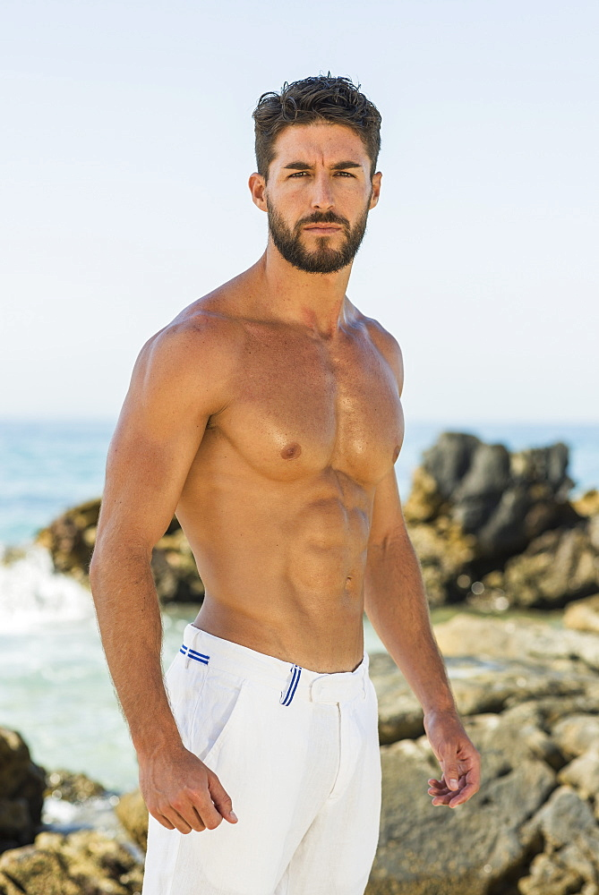Portrait Of A Shirtless Man Wearing White Shorts On The Rocky Coast, Tarifa, Cadiz, Andalusia, Spain