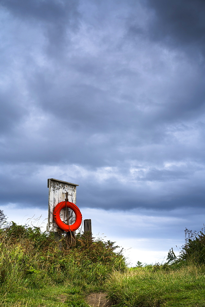 Red Ring Life Preserver Hanging On A Wooden Post, Northumberland, England